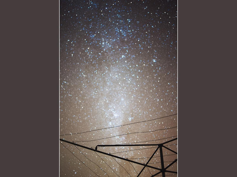 A long exposure of the night sky and stars with a hills hoist in the foreground at my grandpas house
