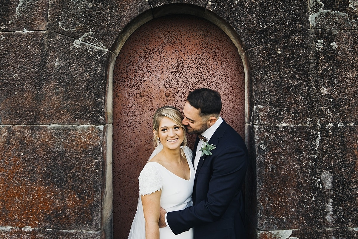 Bride and Groom infront of the red stone wall and red door at Gunners Barracks