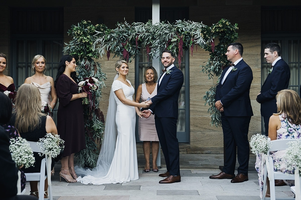 Bride and groom during their wedding ceremony in the sandstone courtyard at Gunners Barracks