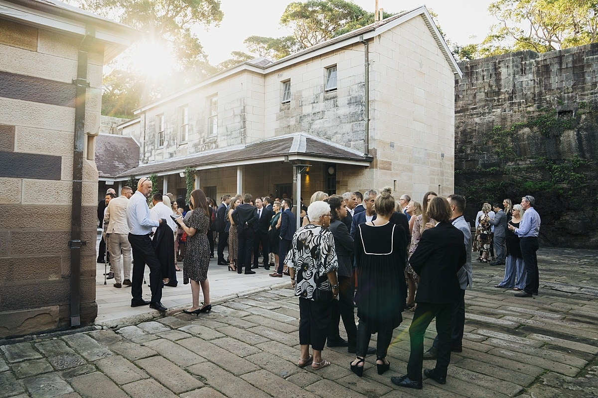 Wedding guests mingling in the sandstone courtyard at Gunners Barracks
